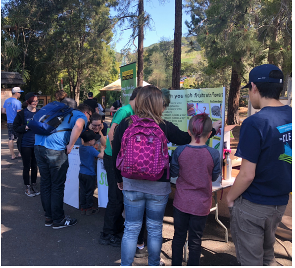 Groups of families visit our Flowers and Pollinators table on Earth Day at the Oakland Zoo.